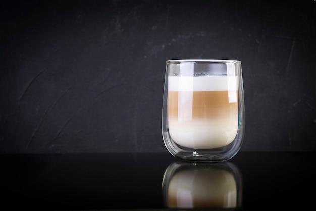커피 마끼아또 한잔. 어두운 배경에 뜨거운 음료 커피