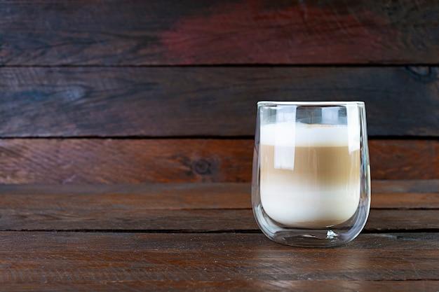 一杯のコーヒーマキアート。木製の背景にホットドリンクコーヒー