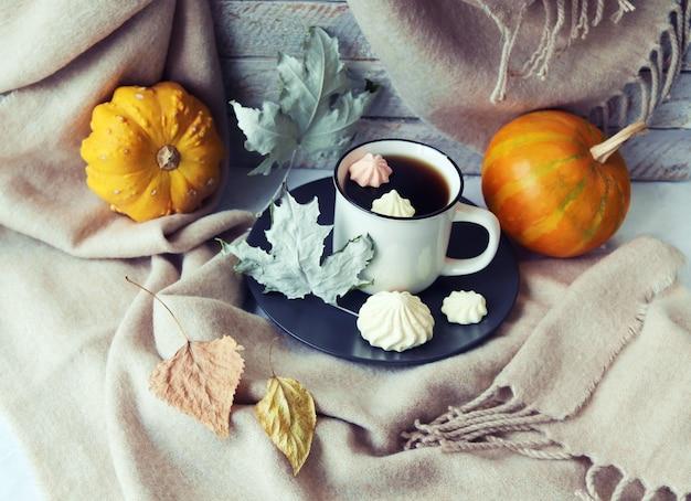 一杯のコーヒーメレンゲカボチャは、窓辺の家の快適さの概念に暖かい毛布を残します