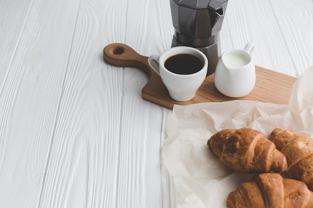 Чашка кофе возле круассанов Бесплатные Фотографии