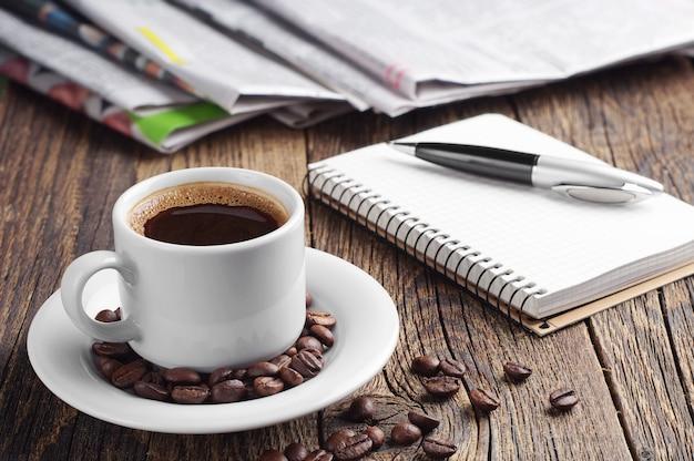一杯のコーヒー、新聞、メモ帳、古い木製のテーブルの上にペン