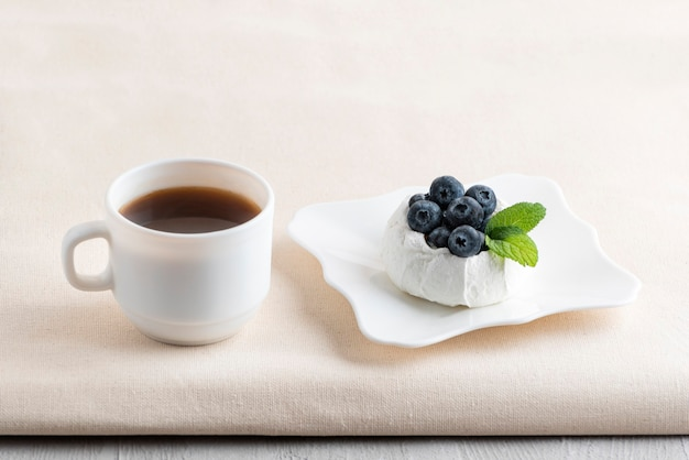 Чашка кофе рядом с ягодным десертом. свежий черничный торт безе и чай.