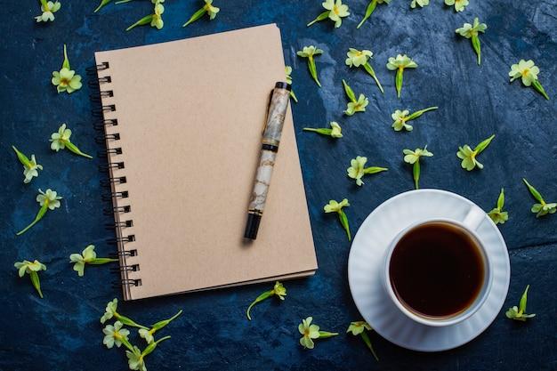 一杯のコーヒー、ノートブック、暗い青色の背景に花。フラットトップビュー