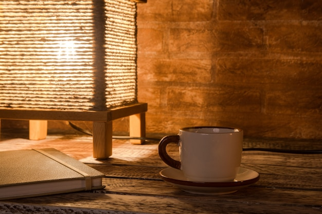 一杯のコーヒー、ノートブック、ビンテージテーブルランプ