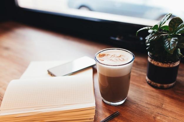 카페 테이블에 커피, 노트북, 전화의 컵. 배경을 흐리게.