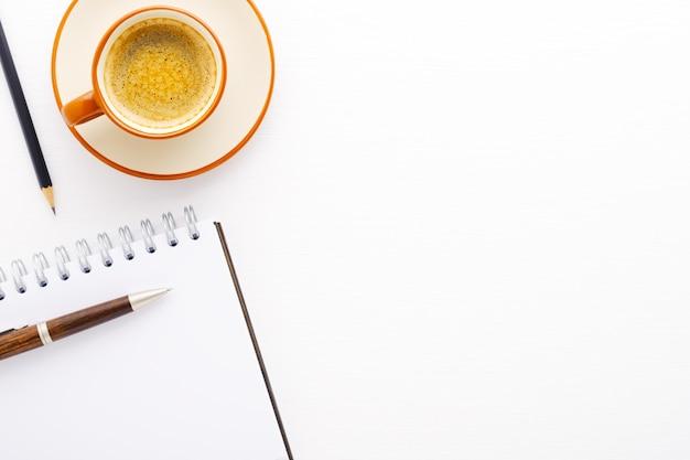 Чашка кофе, блокнот и ручка на белой деревянной предпосылке. вид сверху на рабочем месте. место для надписи