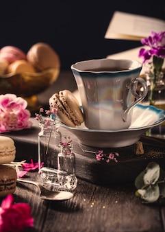 Чашка кофе, старые книги и розовые цветы гвоздики на старой деревянной поверхности. день матери, поздравительная открытка дня рождения. копировать пространство