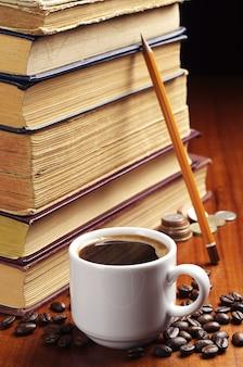 Чашка кофе, старые книги, карандаш и монеты на столе
