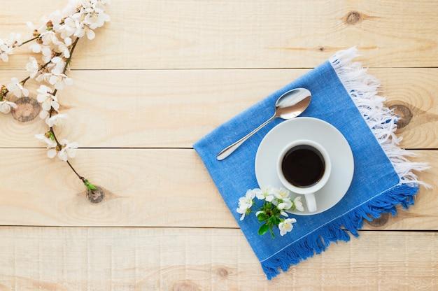 블루 냅킨에 커피 한잔. 봄 꽃. 상위 뷰.