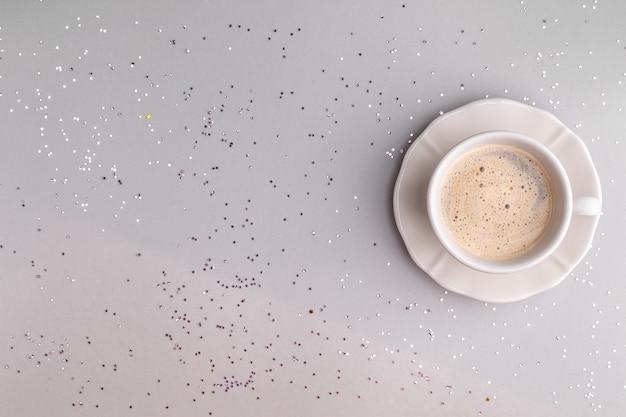 お祝いの灰色のテーブルの上のコーヒーのカップ。フラットスタイル。スペースをコピーします。上からの眺め。