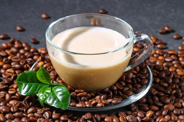 コーヒー豆とコーヒーの葉と灰色のテーブルの上のコーヒーのカップ