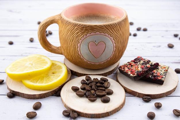 軽い木製のテーブルの上のコーヒーのカップ。近くには黄色いジューシーなレモン、コーヒー豆がテーブルに散らばっているダークチョコレートがあります。上からの眺め。