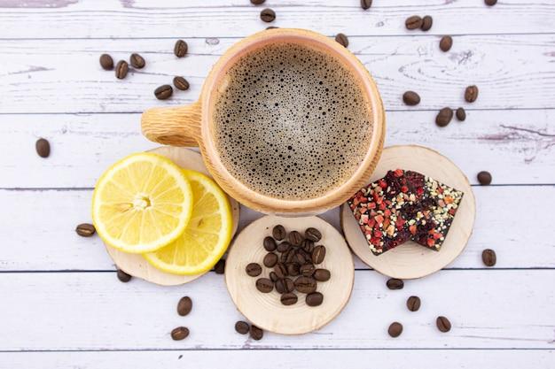 Чашка кофе на светлом деревянном столе. рядом лежит желтый сочный лимон, темный шоколад с разбросанными по столу кофейными зернами. вид сверху.