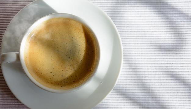 창 근처 테이블에 커피 한잔. 창틀의 그림자