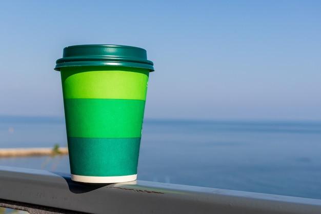 青い空と空の海のビーチサイドのテーブルの上のコーヒーのカップ。夏休みのコンセプト。モックアップ、コピースペース