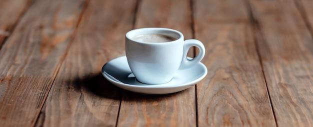 古い木製のテーブルの上のコーヒーのカップ。白いセラミック。泡のある芳香族コーヒー