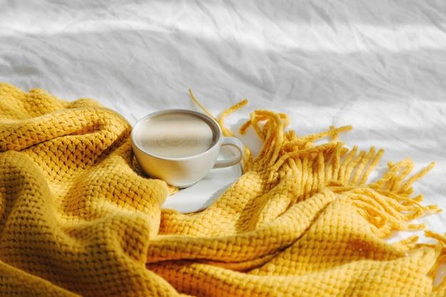 Чашка кофе на кровати с теплым пледом. осенняя концепция.