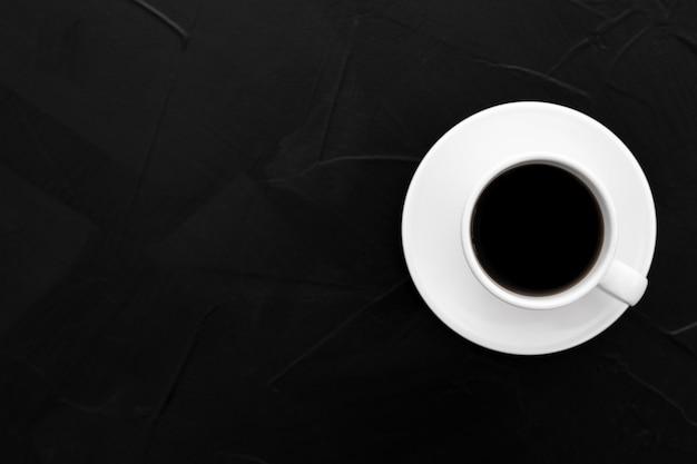 黒のテクスチャ背景にコーヒー1杯