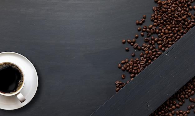 텍스트를 위한 검은색 나무 바닥 배경 상단 보기 공간에 있는 커피 한 잔