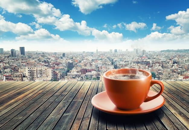 街の背景にコーヒーのカップ