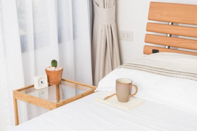 Чашка кофе на уютной белой кровати с цветочным горшком кактуса