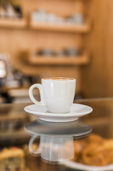 Cup of coffee on glass counter in caf�