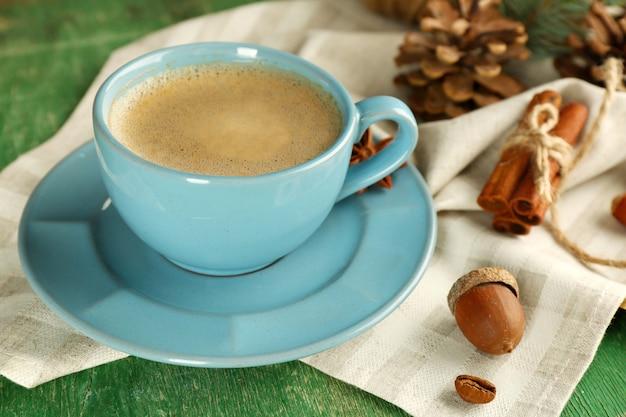 緑の木製の背景にナプキンのコーヒーのカップ