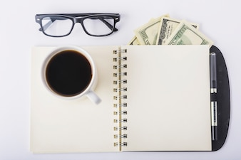 Cup of coffee on notebook with glasses on desk