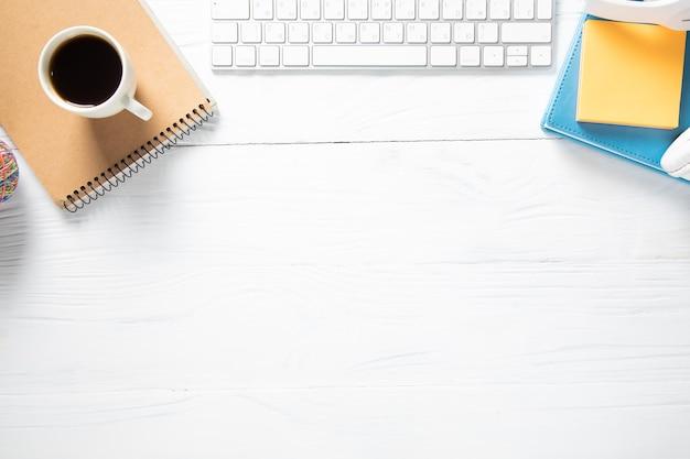 Чашка кофе в блокноте с компьютером на рабочем столе