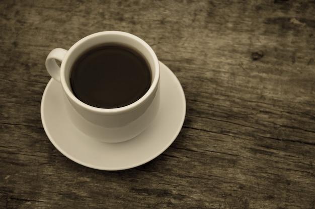 素朴な木製のテーブルの上のコーヒーのカップ