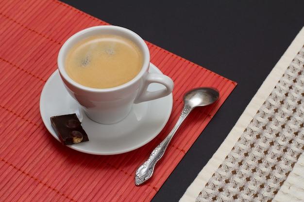 黒の背景にチョコレートバー、スプーン、竹ナプキン、キッチンタオルの部分と受け皿にコーヒーのカップ。上面図。