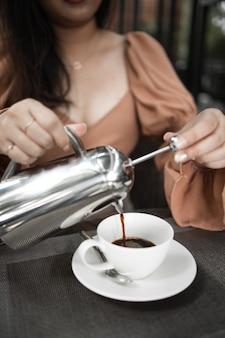 Чашка кофе на столе в кафе. утренний кофе, попивая горячий кофе и наслаждаясь утренним расслабленным настроением