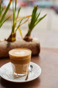 窓の近くのカフェのテーブルの上のコーヒーのカップ