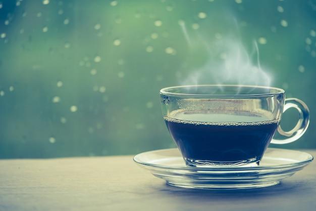 窓の中のテーブルの上のコーヒーのカップ、雨の日の朝のコーヒーブレーク
