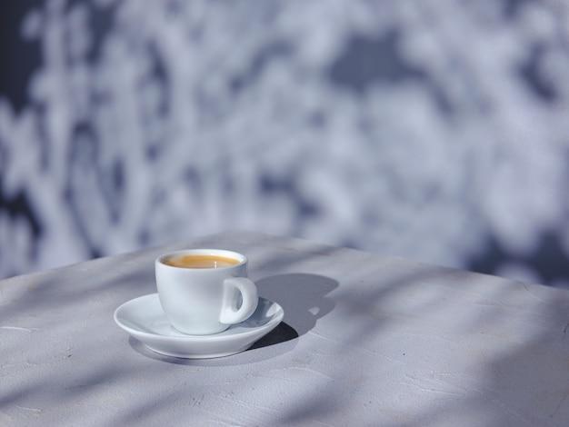 自然光と影とテーブルの上のコーヒーのカップ