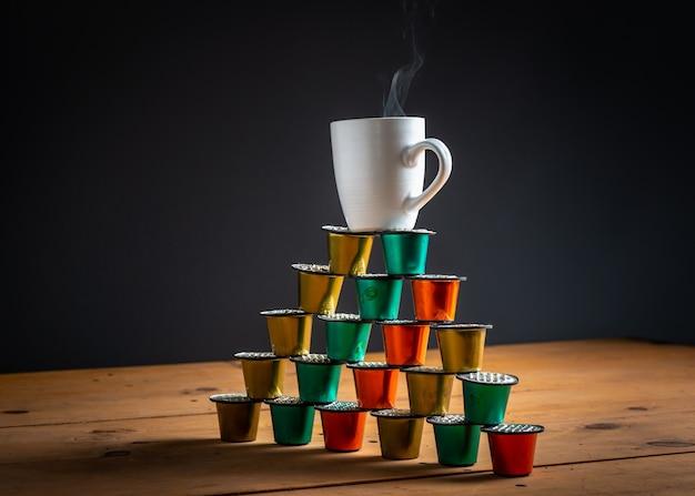 Чашка кофе на вершине башни, сделанной из цветных кофейных капсул и используемой на деревянном столе