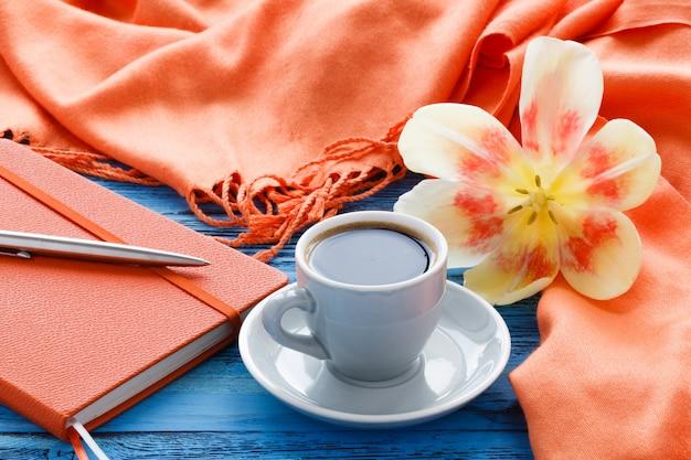 チューリップの開いている花とターコイズブルーの木製テーブルの上のコーヒーカップ