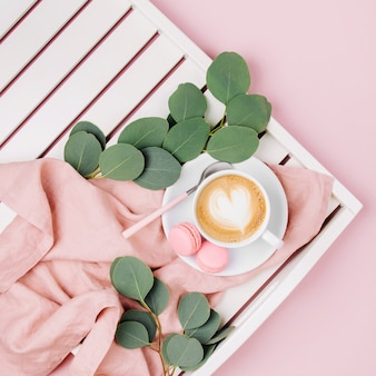 Чашка кофе на белом деревянном подносе и ветви эвкалипта. плоская планировка, вид сверху