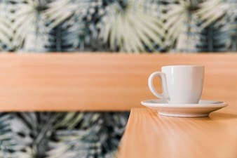 Cup of coffee on wooden desk in caf�