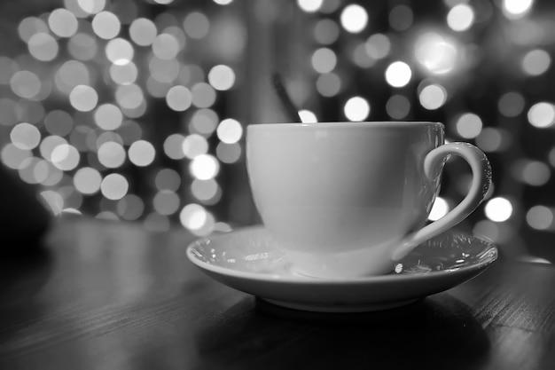 カフェの木製テーブルの上のコーヒーのカップは、背景のライトをぼかします