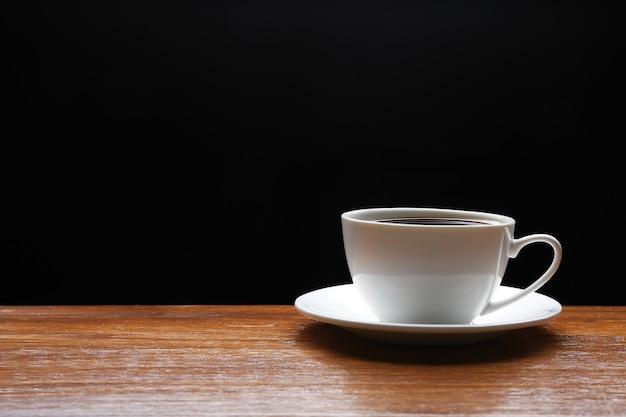 黒の背景に木製のテーブルの上のコーヒーのカップ