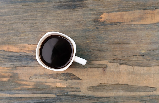Чашка кофе на деревянном столе, вид сверху