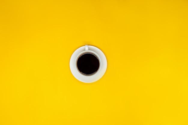 黄色の表面にコーヒー1杯