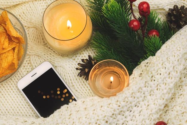 燃えるろうそくと輝くクリスマスライトの上にベッドで編まれた灰色のセーターと一緒に開いた本にとどまる一杯のコーヒーまたは紅茶がクローズアップします。冬のホリデーシーズン。上面図。 。高品質の写真