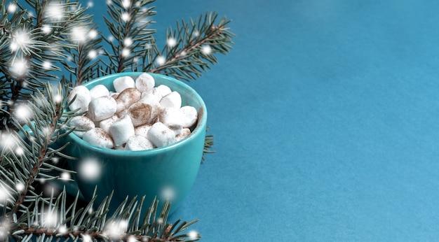 Чашка кофе или какао с зефиром и еловыми ветками с нарисованным снегом на бирюзовом заделывают. концепция домашнего уютного отдыха. рождественский фон. горизонтальная ориентация. скопируйте место для текста.