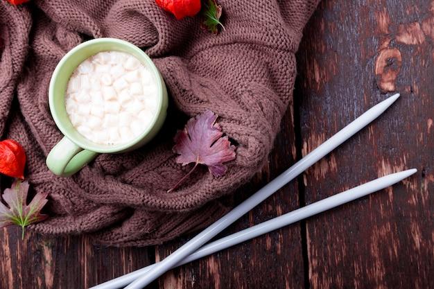 ニットブランケットと編み針の近くにマシュマロとコーヒーまたはホットチョコレートのカップ。秋のコンセプト。上面図。