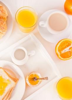 一杯のコーヒーまたは紅茶、オレンジジャムとトースト、白い表面にオレンジジュースのグラス。朝食のコンセプトです。上面図。