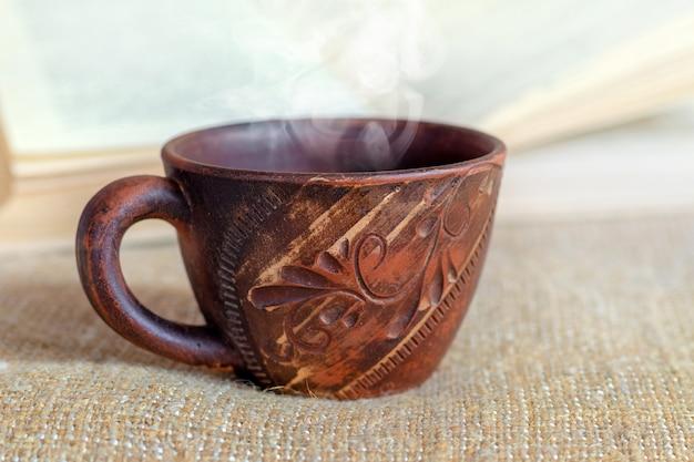 開いた本の近くで一杯のコーヒーまたはお茶