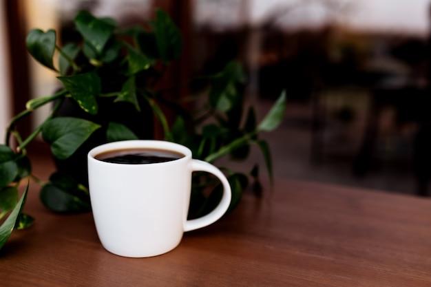 Чашка кофе или чая на столе на деревянной коричневой террасе во время заката. расслабление, концепция тихой сельской жизни