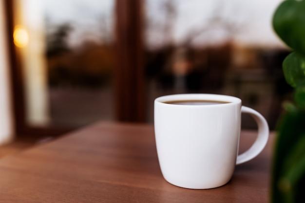 배경을 흐리게 일몰 동안 나무 갈색 테라스에 테이블에 커피 또는 차 한잔. 휴식, 조용한 시골 생활 개념
